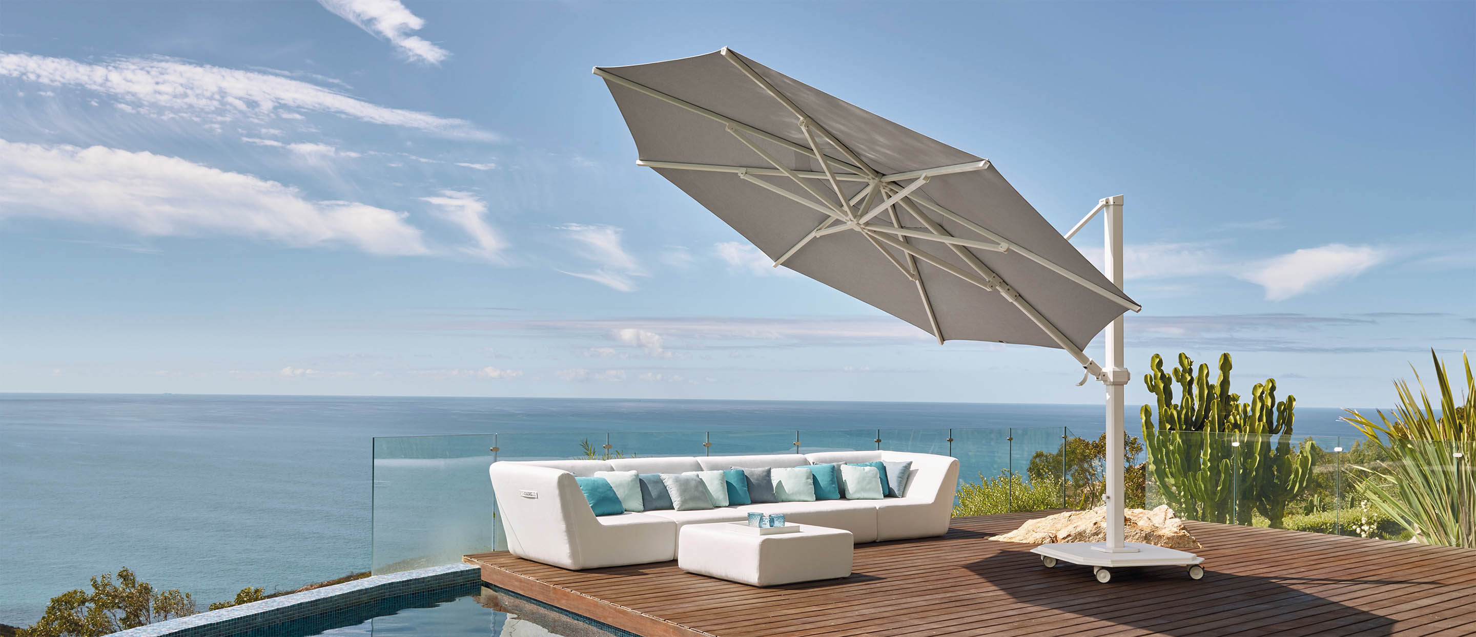 A photo of a large cantilever umbrella shading a white sectional on a patio