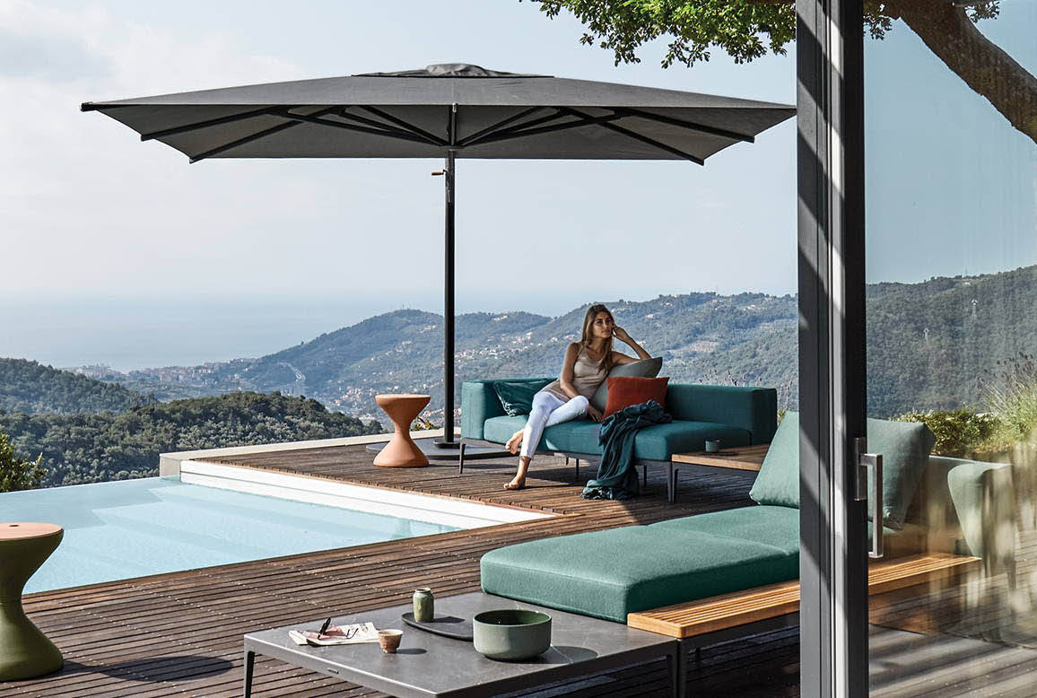 A stylishly dressed woman sitting on a sofa under a market style umbrella next to a sparkling blue pool