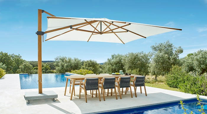 An umbrella covering a dining set in between two pools