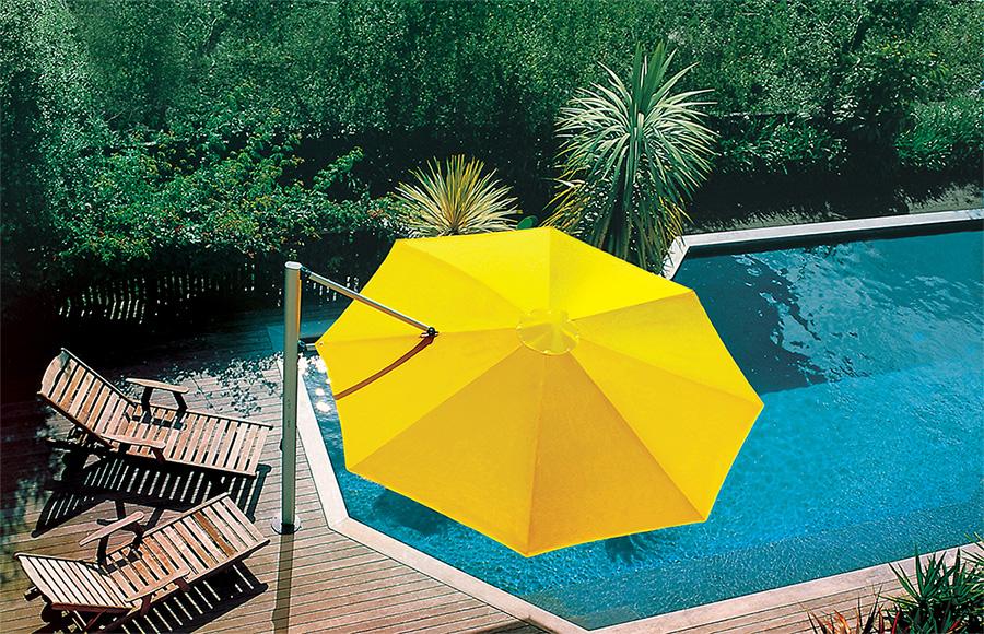 A hexagonal yellow umbrella by a pool